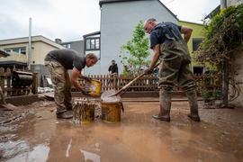 Mit Eimern entsorgen Anwohner die Schlammmassen nach dem Hochwasser der Kyll. Zahlreiche Häuser im Ort waren betroffen, Bewohner mussten evakuiert werden.