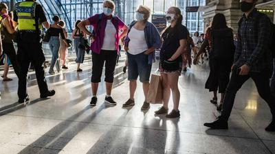 Menschen mit Mund-Nasen-Schutz stehen in einer U-Bahn Station in London.