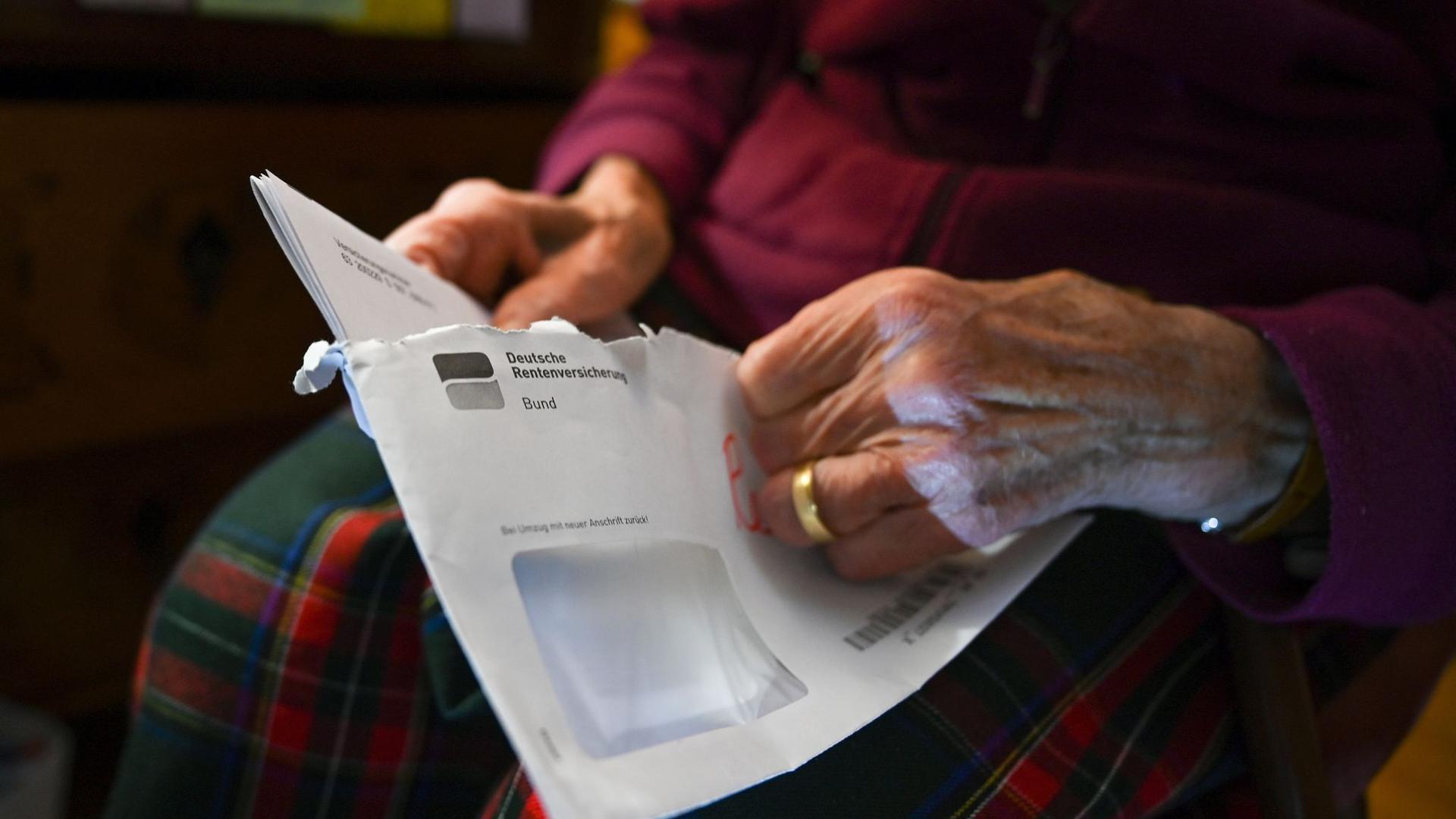 Eine Seniorin hält ihren Rentenbescheid in der Hand.