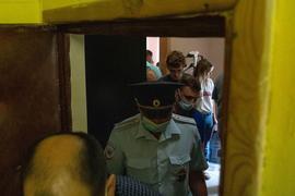 Polizisten verlassen die Wohnung der Journalistin Maria Zholobova in Moskau.