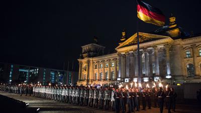 Zahlreiche Soldaten stehen bei einem Großen Zapfenstreich vor dem Reichstagsgebäude in Berlin.