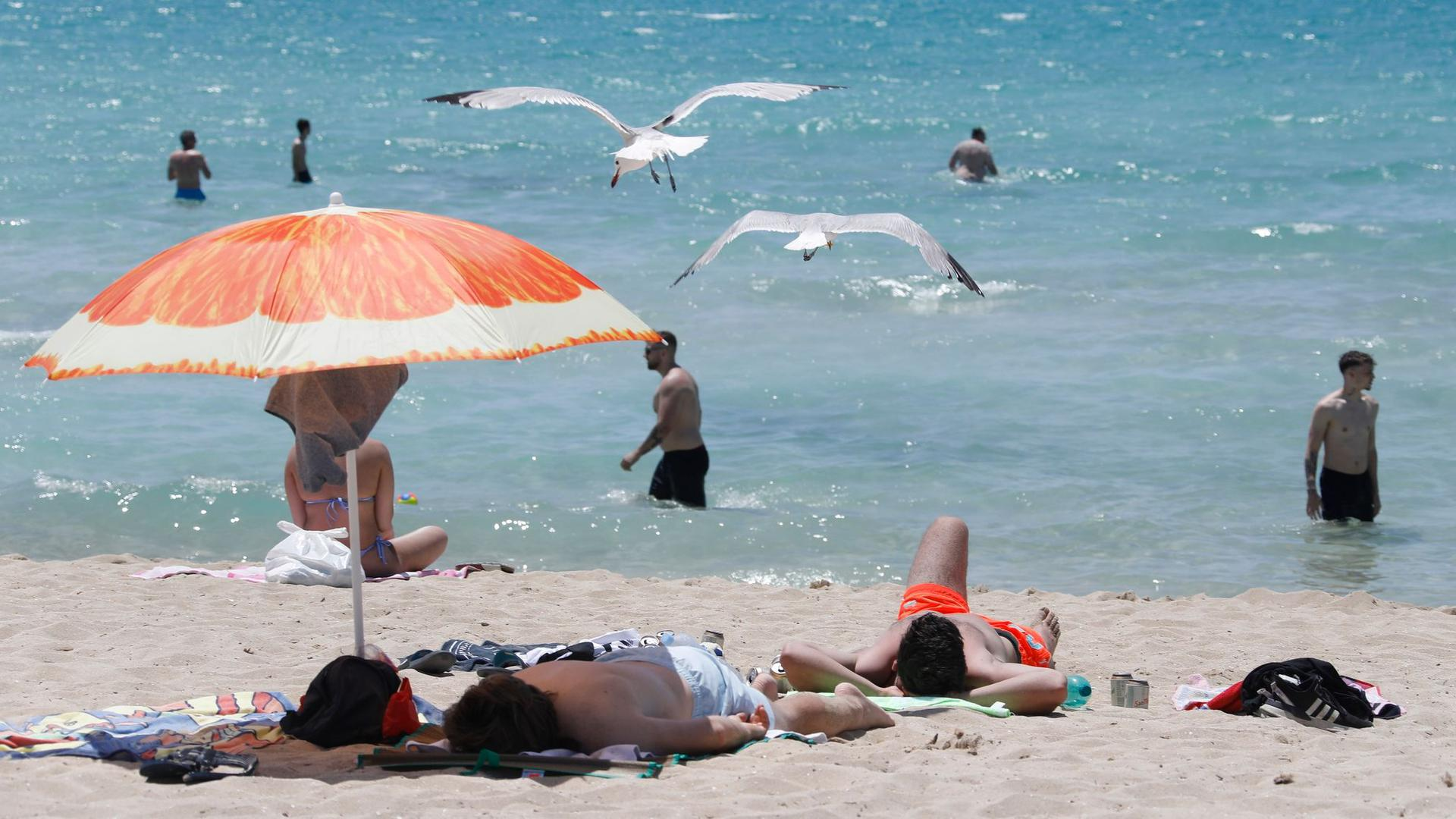 Touristen genießen die Sonne am Strand von Arenal.