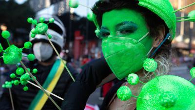 Ein Demonstrantin hat sich ihr Gesicht grün geschminkt und trägt eine grüne Schutzmaske. Tausende Brasilianer sind erneut gegen die Corona-Politik der Regierung von Bolsonaro auf die Straße gegangen.