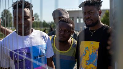 Migranten aus Kamerun stehen am Zaun eines Flüchtlingslagers in Litauen.