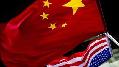 Die US-amerikanische (unten) und chinesische Nationalflaggen wehen vor einem Hotel in Peking.