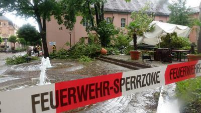 Am Schlossplatz in Rastatt in Baden-Württemberg liegt ein großer Baum auf den Tischen eines Restaurants.