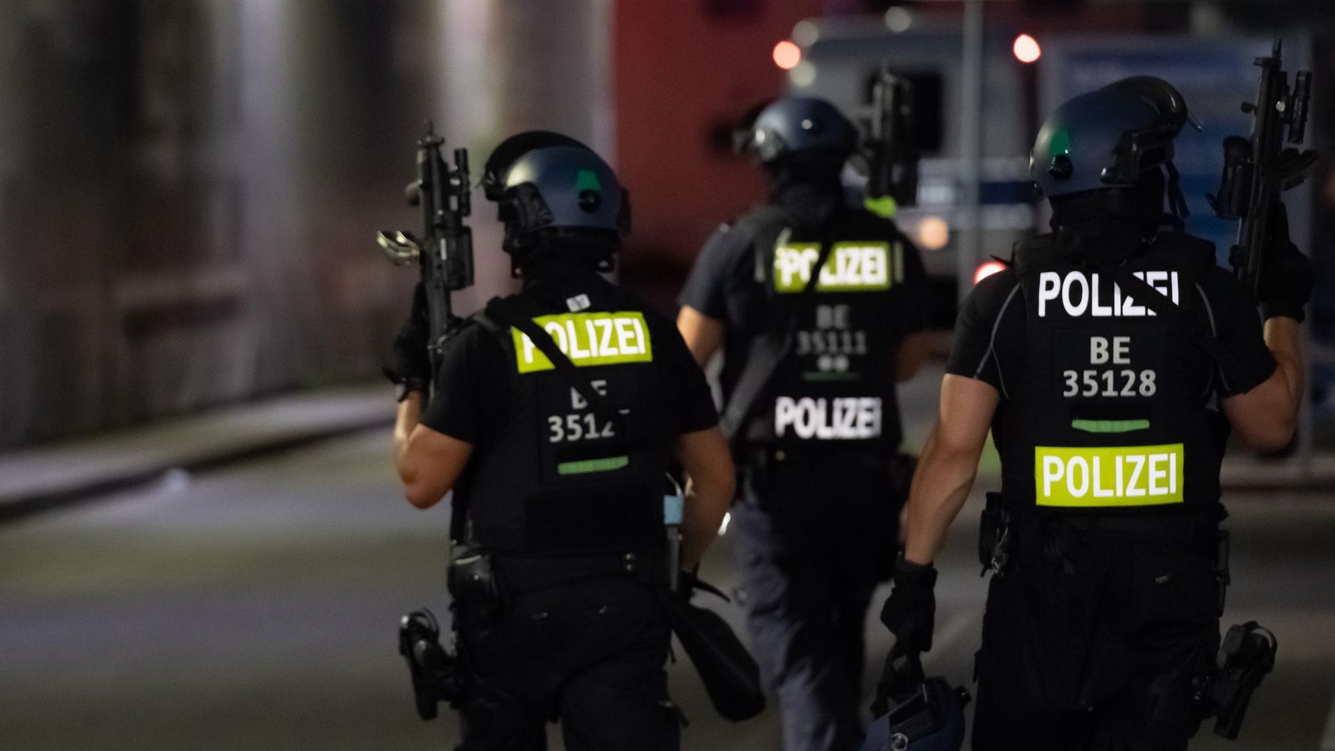 Polizisten mit Maschinenpistolen suchen auf dem Gelände eines Baumarktes in Berlin-Wedding nach Verdächtigen.