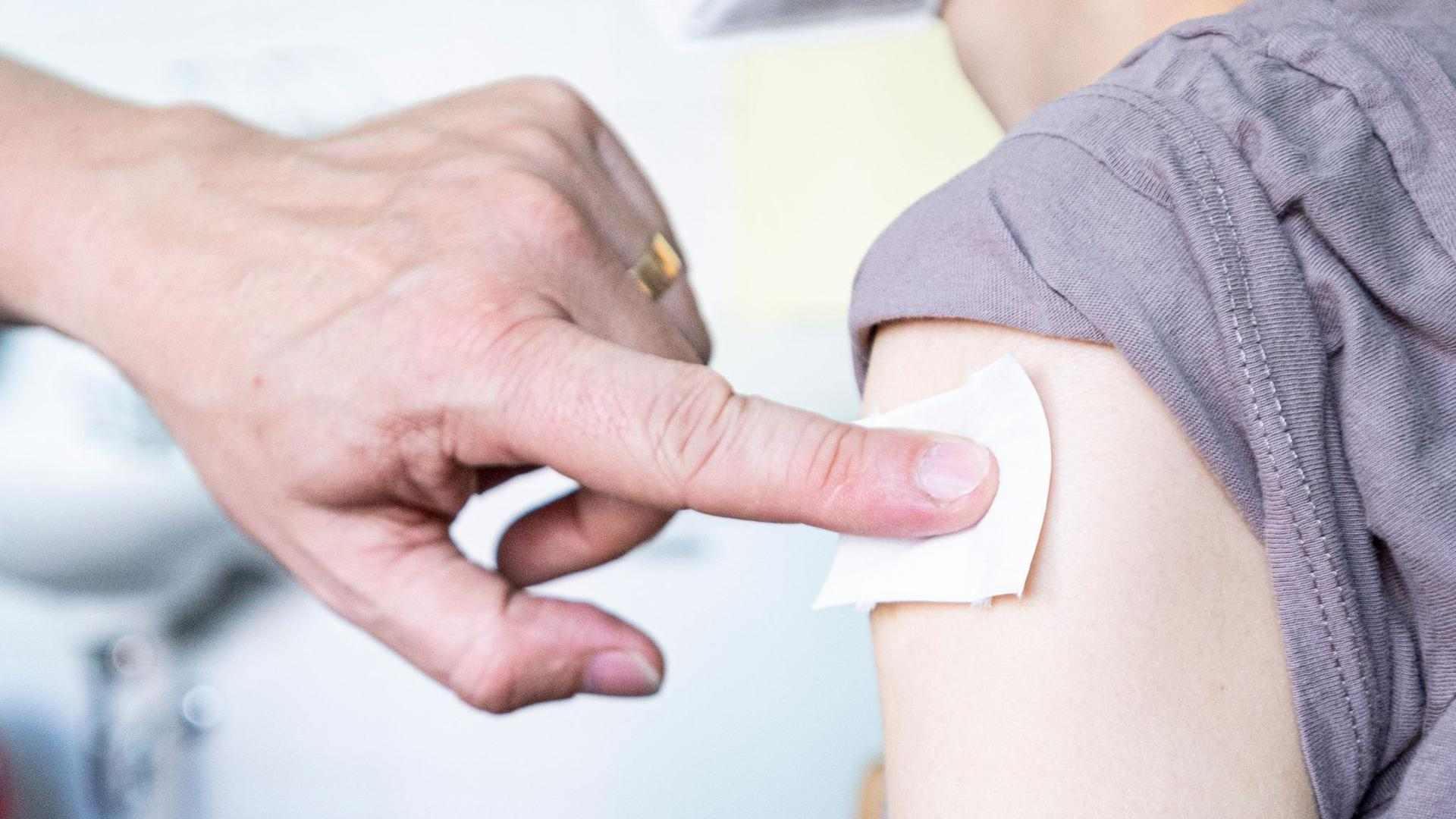 Ein Kinder- und Jugendarzt drückt ein Abtupftuch an die Stelle einer Impfung.