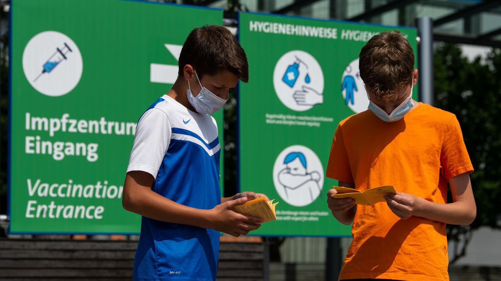 Die Geschwister-Impflinge Hugo (12 Jahre) und Urs (13 Jahre) blättern vor ihrer Impfung in ihren Impfbüchern.