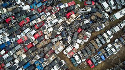Autowracks, die von der Flut der Ahr durch die Straßen gespült wurden, werden auf einem Gelände gesammelt, um sie zur Verschrottung weiterzutransportieren.
