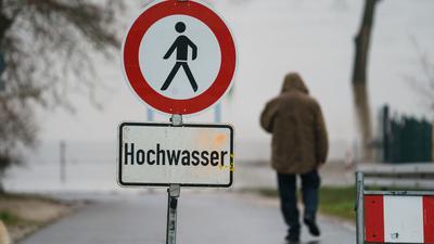 Ein Schild weist Anfang Februar am Rheinufer im hessischen Eltville auf die Gefahr durch Hochwasser hin.