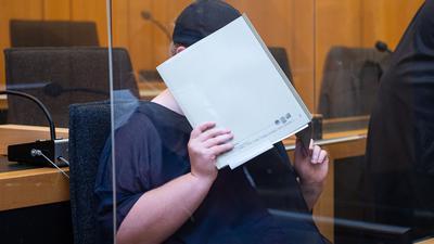 Zu Beginn des Prozesses im Missbrauchskomplex Münster sitzt die Mutter eines Opfers im Landgericht Münster und verdeckt ihr Gesicht mit einer Mappe.