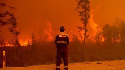 Ein Feuerwehrmann beobachtet westlich von Jakutsk in Russland einen Waldbrand.