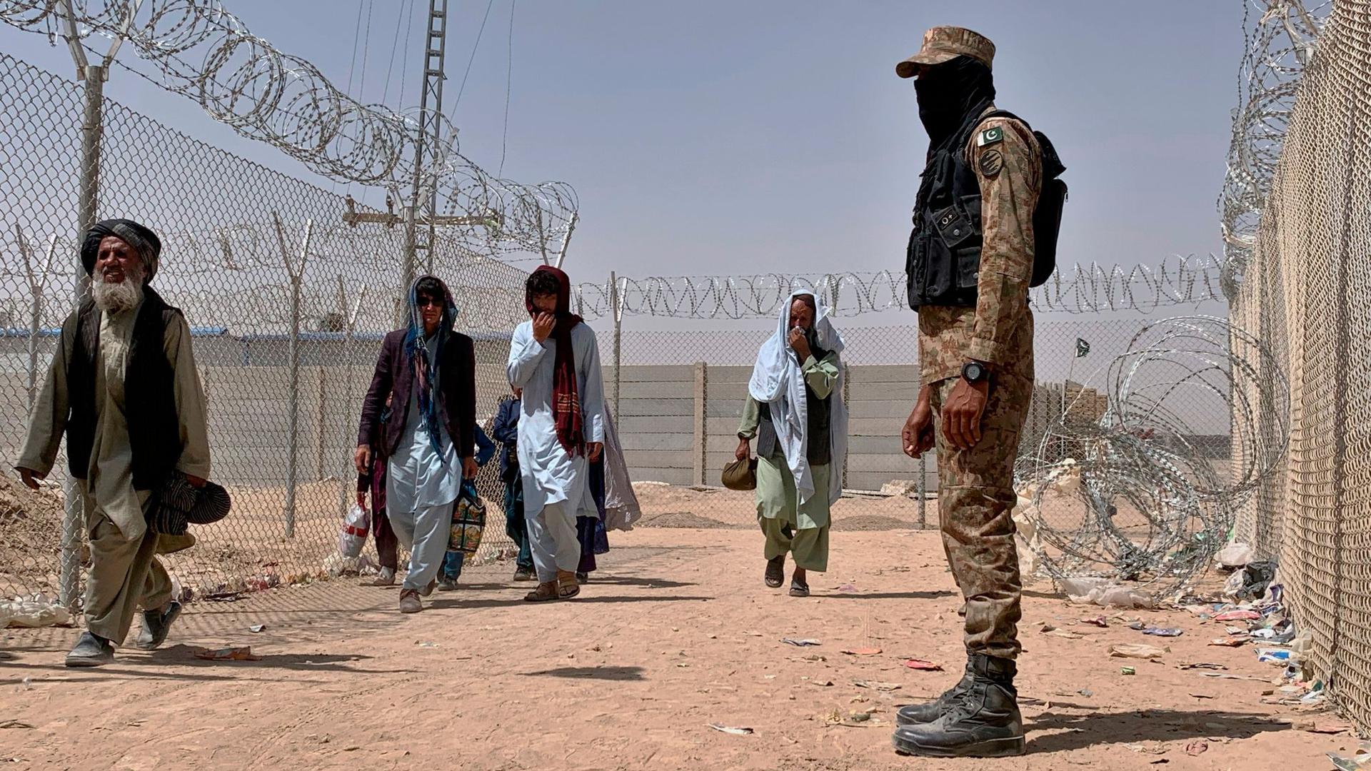 Ein pakistanischer Soldat steht Wache, während Menschen aus Afghanistan über einen Grenzübergang in Chaman nach Pakistan einreisen.