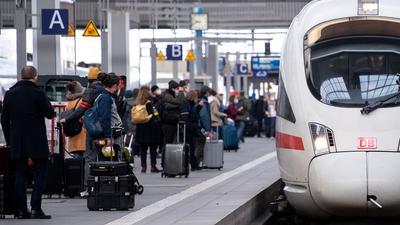 Reisende neben einem ICE am Münchener Hauptbahnhof.