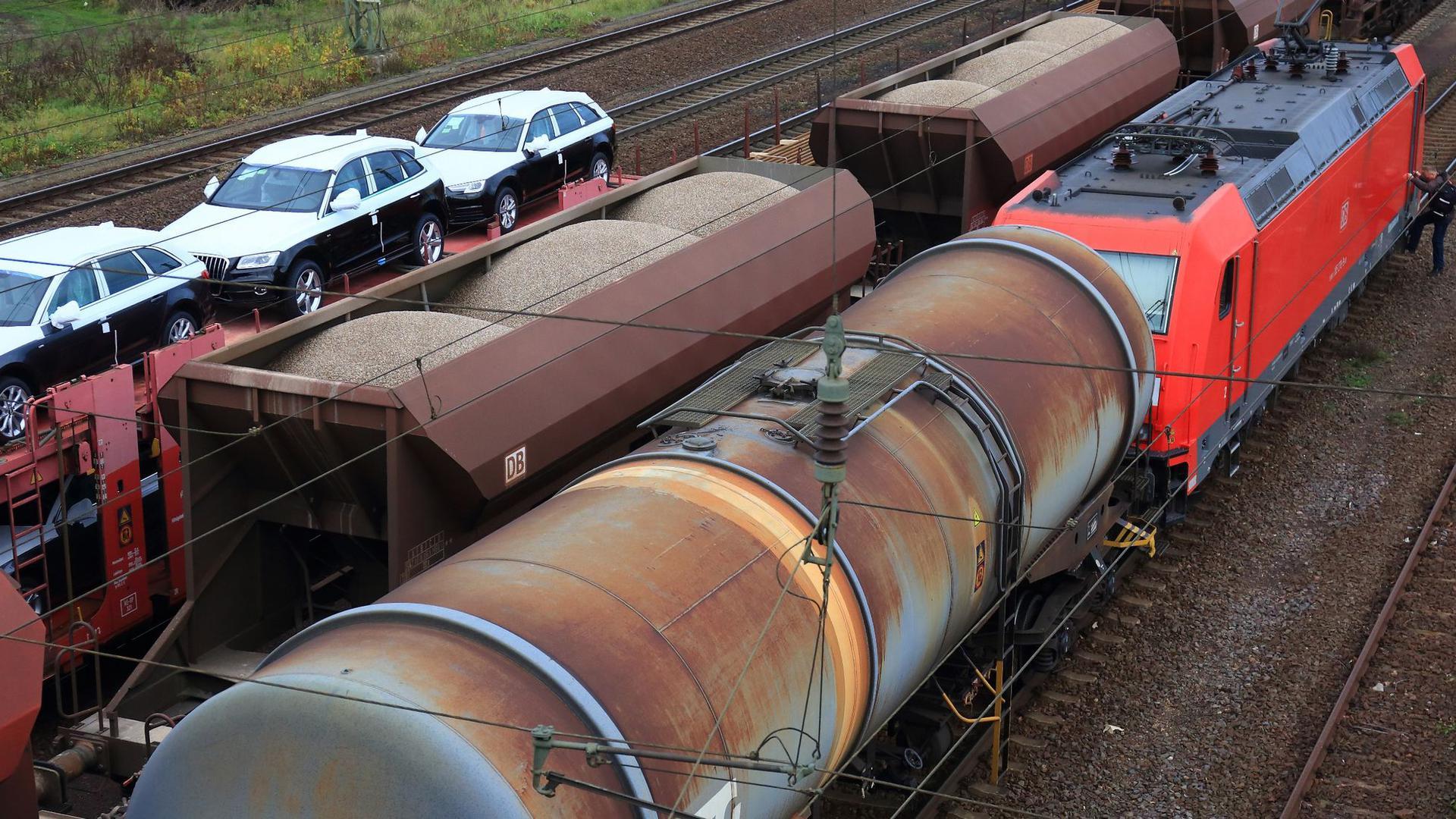 Eine Lokomotive zieht  einen Güterzug mit Kesselwagen in Magdeburg (Sachsen-Anhalt) an einem Zug mit Autos und einem mit Schüttgut vorbei.