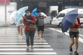 Menschen mit Regenschirmen kämpfen in Keelung gegen das Unwetter.