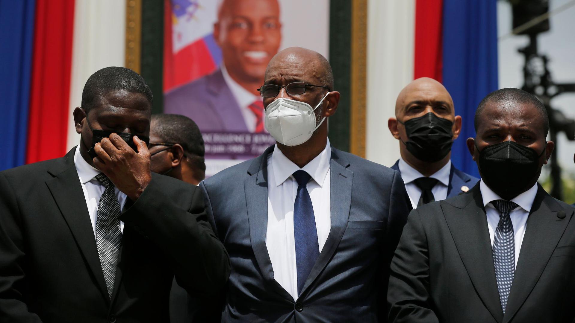 Ariel Henry (M), designierter Premierminister von Haiti, und Interims-Regierungschef Claude Joseph (r) stehenvor einem Porträt des ermordeten haitianischen Präsidenten Jovenel Moise.
