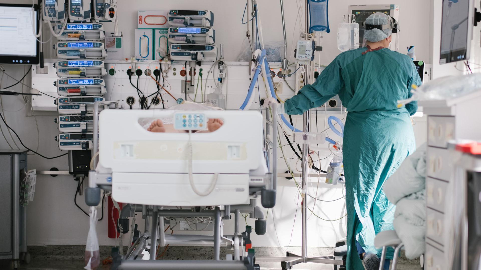 Eine Intensivpflegerin versorgt auf einer Braunschweiger Intensivstation einen an Covid-19 erkrankten Patienten.