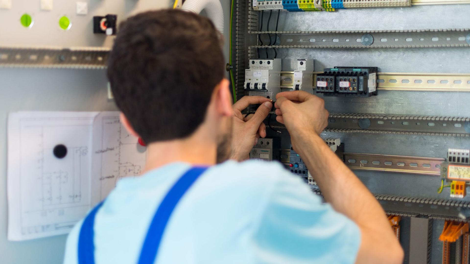 Der 19-jährige Mohammad aus Afghanistan arbeitet in einem Leipziger Ausbildungszentrum von Siemens an der Verdrahtung eines Schaltschranks.