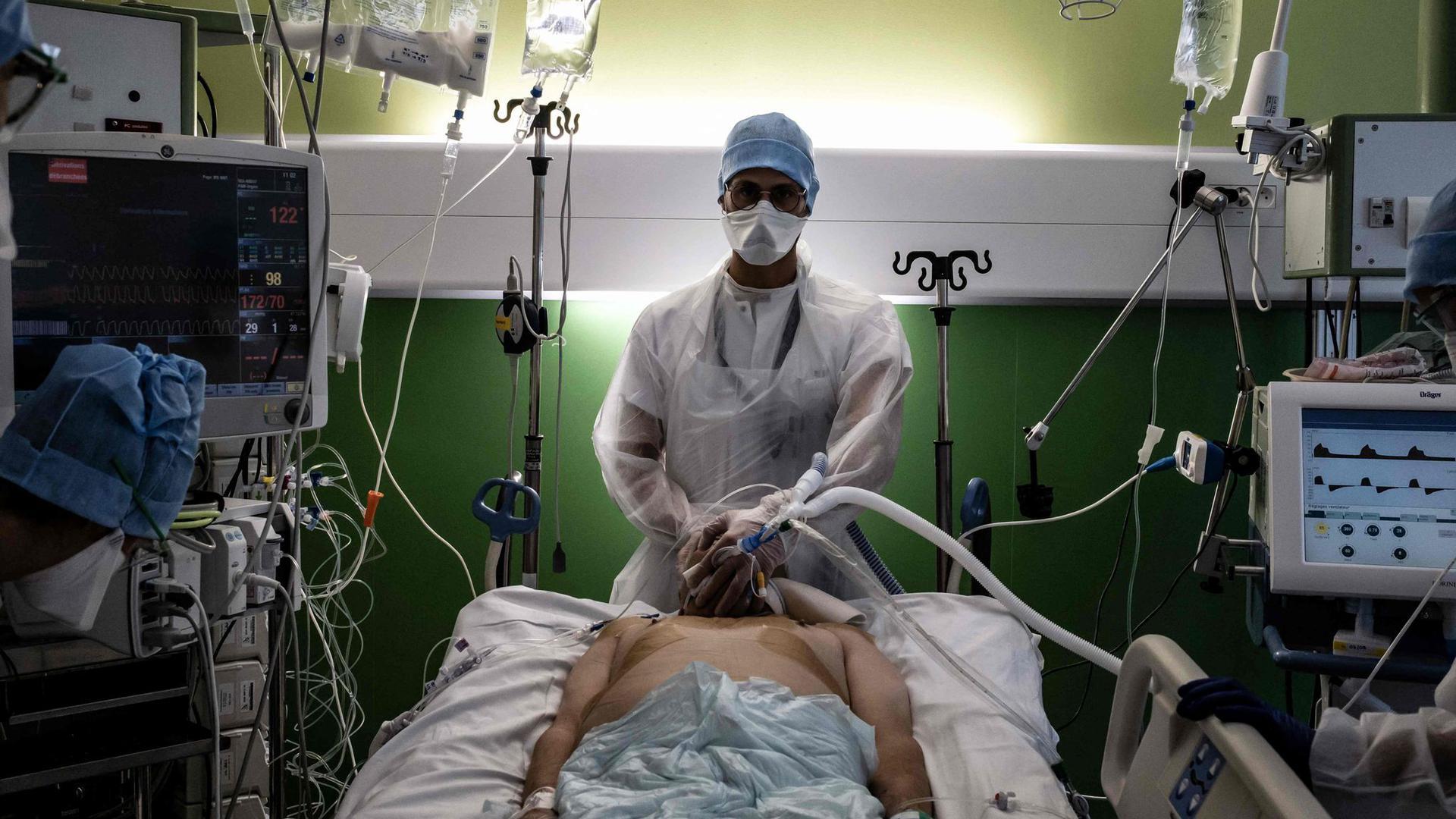 Ein medizinischer Angestellter (M) kümmert sich auf der Intensivstation eines Krankenhauses in Pierre-Benite um einen Corona-Patienten.