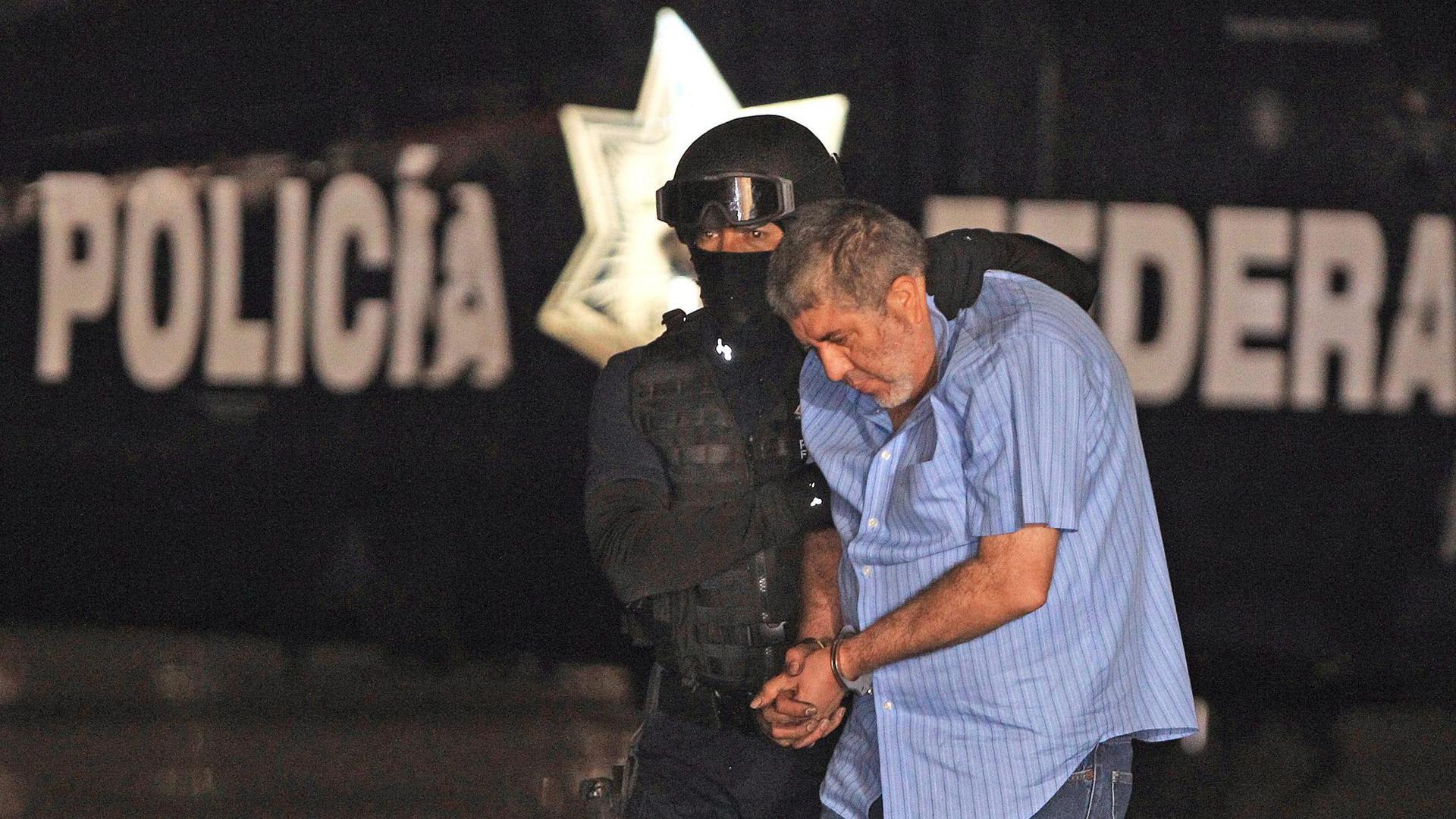 """Vicente Carrillo Fuentes alias """"El Viceroy"""" wird von einem Polizisten abgeführt (2014)."""