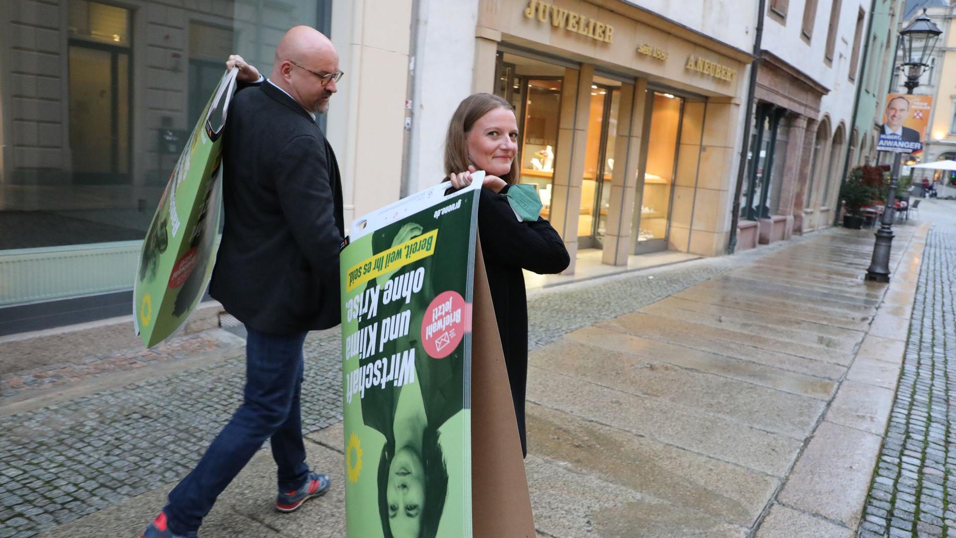 Wolfgang Wetzel, (l) Spitzenkandidat der Grünen und Christin Furtenbacher, Landesvorstandssprecherin der Grünen in Sachsen, laufen mit Wahlplakaten durch die Innenstadt von Zwickau.