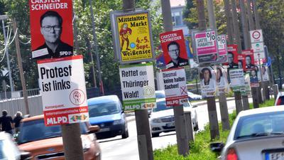 Wahlplakate hängen an Straßenlaternen in der Landeshauptstadt Erfurt in Thüringen.