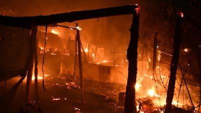 Feuer brennt behelfsmäßige Zelte außerhalb des überfüllten Flüchtlingslagers am Hafen von Vathy auf der ostägäischen Insel Samos ab.