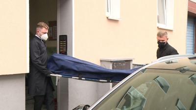 Bestatter bringen das Opfer zu ihrem Fahrzeug.