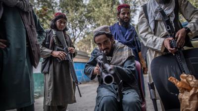 Ein junger Taliban-Kämpfer zielt zum Spaß mit seinem Gewehr in Richtung Fotograf, während er vor einer Polizeistation in Kabul Wache hält.
