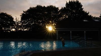 Ein Badegast steigt am frühen Morgen bei Sonnenaufgang ins Schwimmbecken im Freibad Großburgwedel bei Hannover.