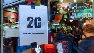 """Im Fenster einer Kiez-Kneipe in Hamburg hängt ein Zettel mit dem Text """"2G, Einlass nur für Geimpfte und Genesene""""."""