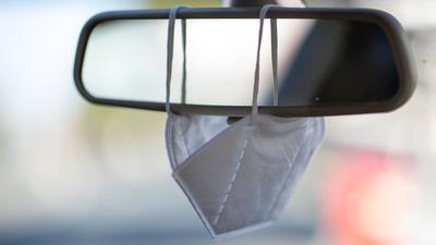 Eine FFP2-Maske hängt am Rückspiegel eines PkWs.