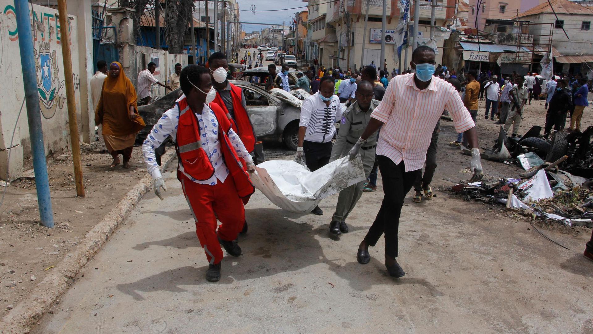 Medizinische Helfer transportieren nach dem Selbstmordattentat ein Todesopfer ab.