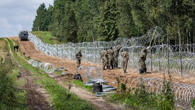 Polnische Soldaten errichten einen Stacheldrahtzaun Grenze zu Belarus (Archiv).