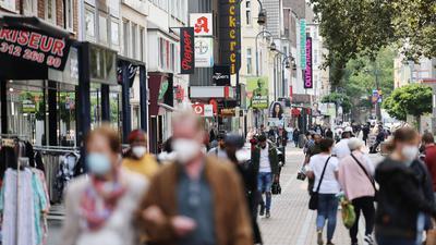 Menschen gehen durch die Fußgängerzone. (Archivbild)