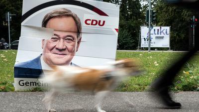 Ein Hund geht an einem beschädigten Wahlplakat vom Armin Laschet (CDU) vorbei.