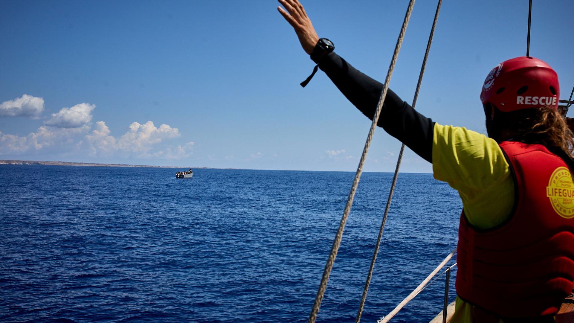 """Ein Mitglied der NGO """"Open Arms"""", die immer wieder Menschen aus dem Mittelmeer rettet, gestikuliert an Bord des Schiffes """"Astral""""."""
