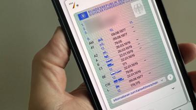 """Ein Mann hält ein iPhone mit der App """"ID Wallet"""", in der die digitale Variante eines Führerscheins zu sehen ist."""