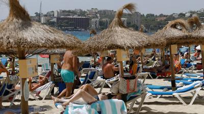Einheimische und Touristen liegen am Strand Cala Major in Palma de Mallorca.