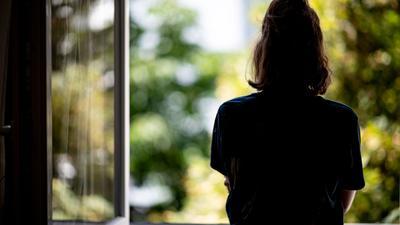 Eine Frau steht in ihrer Wohnung an einem Fenster. (Archivbild)