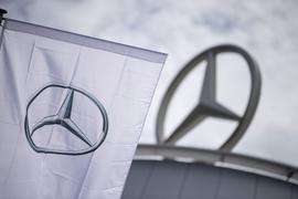 Eine Fahne mit dem Logo der Marke Mercedes-Benz weht vor einem Showroom der Firma.