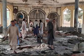 Menschen betrachten die Schäden in der attackierten Moschee in Kundus.