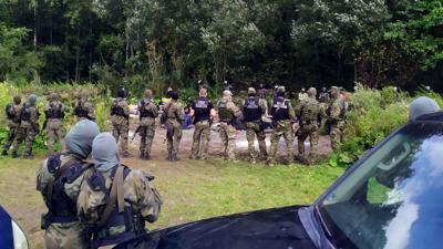Sicherheitskräfte kreisen Migranten ein, die über Belarus nach Polen gereist sind.