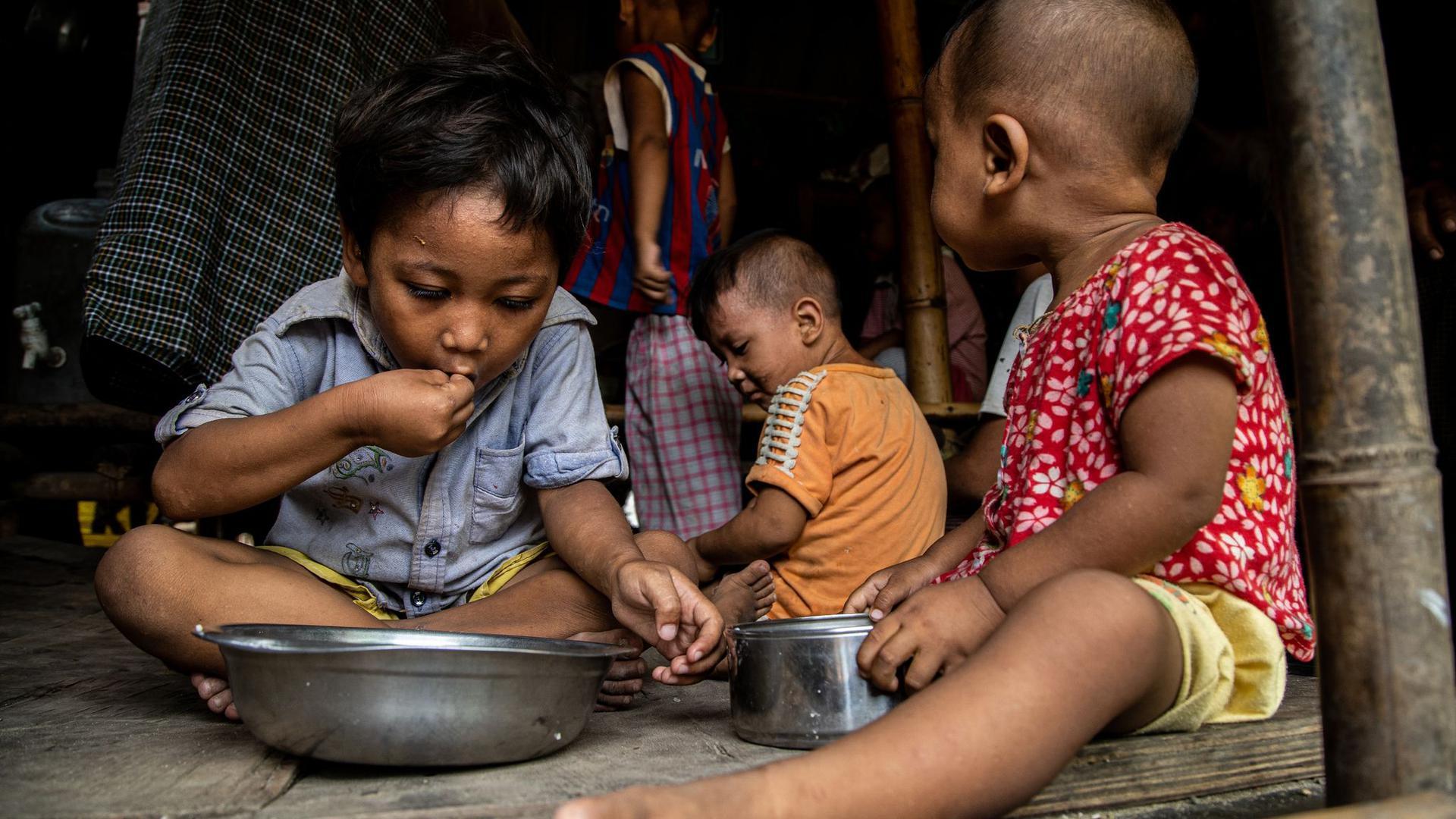 Kinder einer vom World Food-Programme unterstützten Familie sitzen beim Mittagessen in ihrer Hütte im Hlaing Thar Yar Township. (Archivbild)