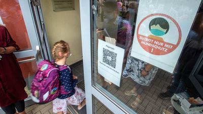 Ein Kind geht mit Maske in eine Schule. Das Robert Koch-Institut (RKI) registriert in einzelnen Regionen Deutschlands besonders viele Corona-Ansteckungen bei Kindern und Jugendlichen.
