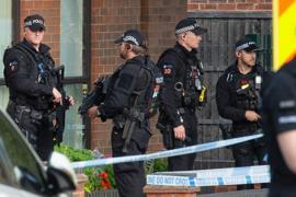 Polizeibeamte und Rettungskräfte stehen am Tatort. Der tödliche Messerangriff wurde jetzt als terroristische Tat eingestuft.