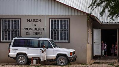 Kinder stehen im Hof des Waisenhauses Maison La Providence de Dieu.