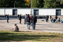 Asylsuchende laufen in der Erstaufnahmeeinrichtung Eisenhüttenstadt über einen Platz. (Archivbild)